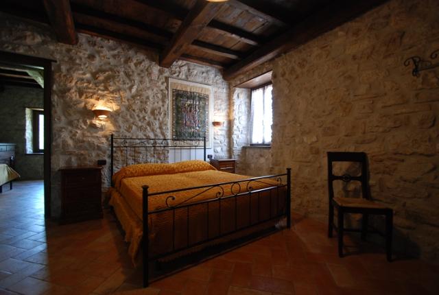 Camere - Camera da letto con parete in pietra ...